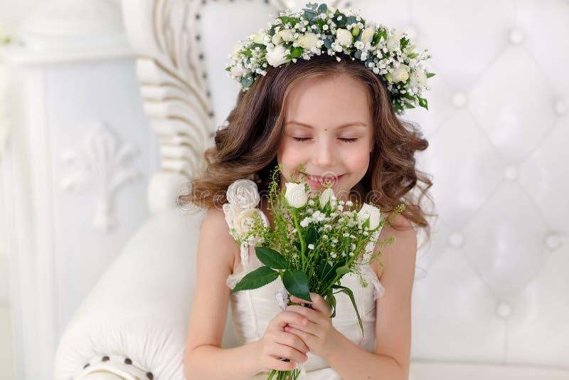 Den gulliga lilla flickan med mörkt hår i en ljus studio med en krona av blommor och en bukett med ögon stängde sig N?rbild arkivbilder