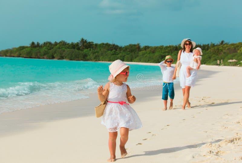 Den gulliga lilla flickan med modern, systern och brodern går på stranden arkivbilder