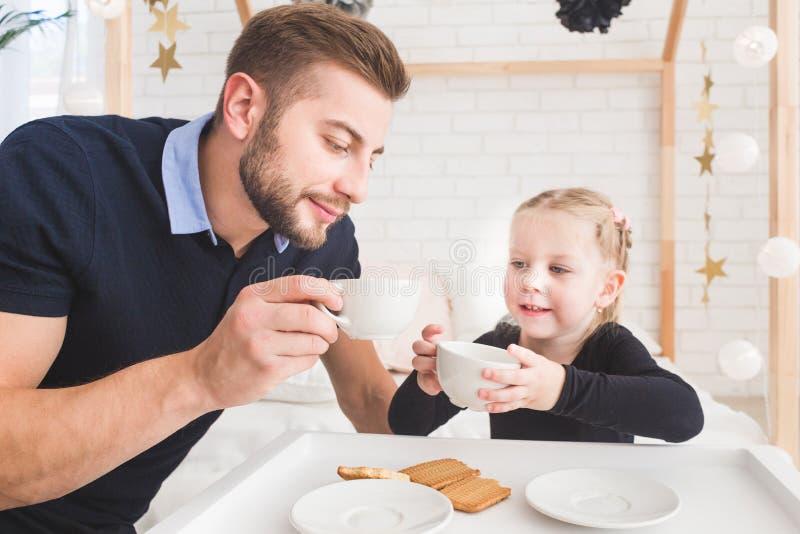 Den gulliga lilla flickan och hennes fader dricker te med kakor hemma royaltyfria foton