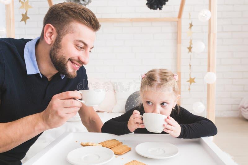 Den gulliga lilla flickan och hennes fader dricker te med kakor hemma arkivbilder