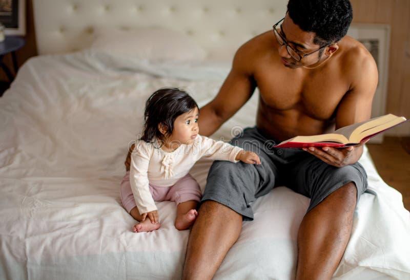 Den gulliga lilla flickan och hennes fader läser en bok, medan sitta på sängen royaltyfri fotografi