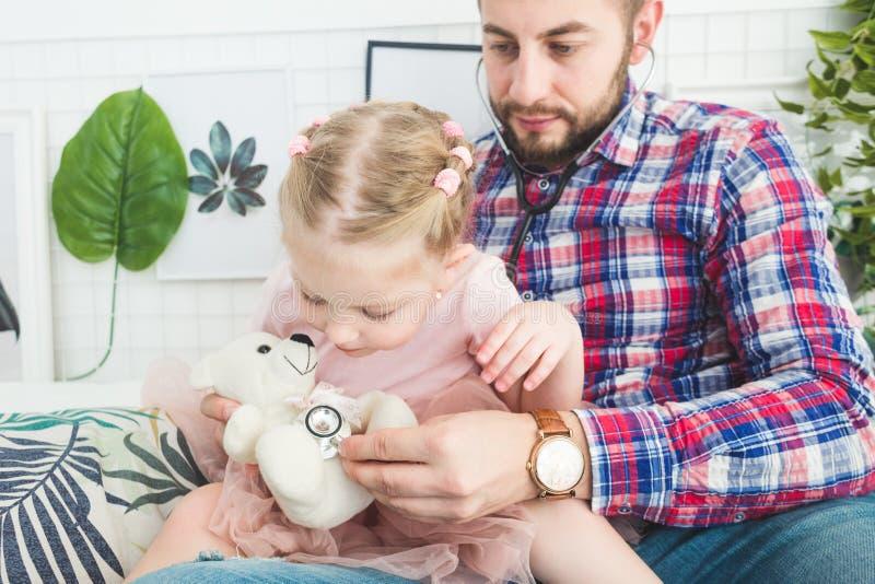 Den gulliga lilla flickan och hennes fader spelar doktorn hemma royaltyfri foto