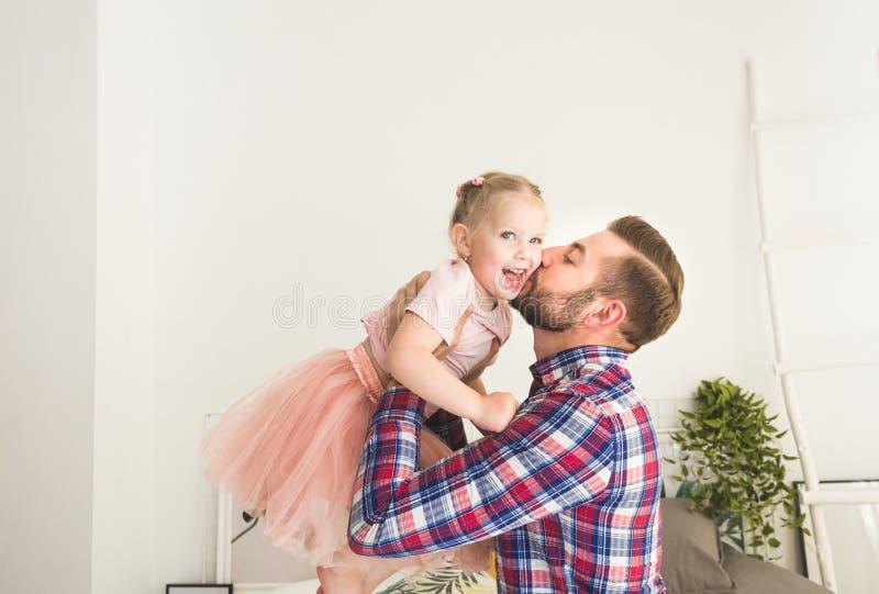 Den gulliga lilla flickan och hennes farsa har gyckel hemma arkivbild
