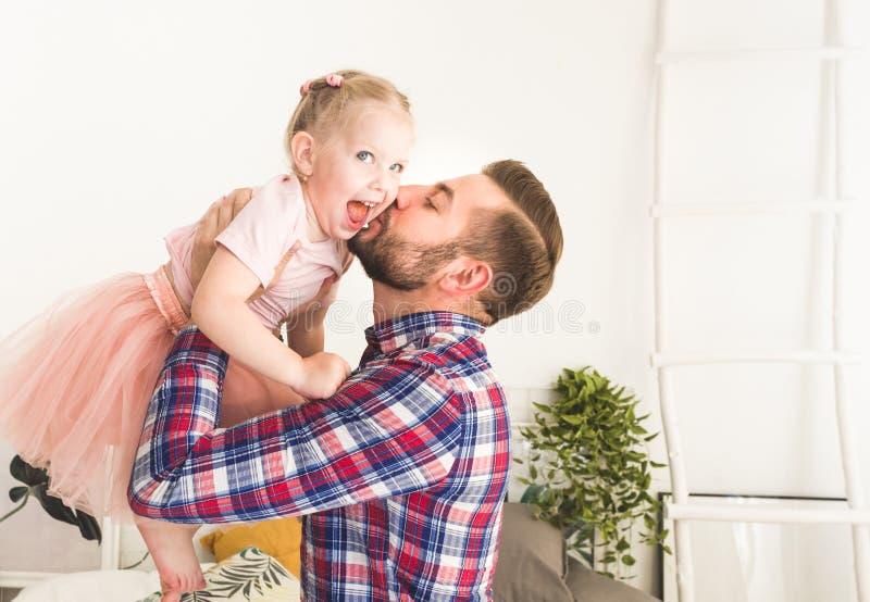 Den gulliga lilla flickan och hennes farsa har gyckel hemma royaltyfri foto