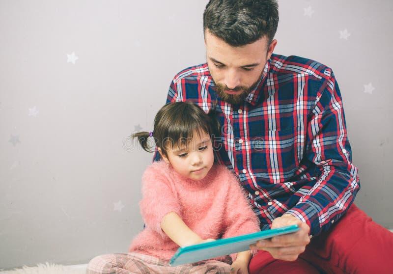 Den gulliga lilla flickan och hennes stiliga fader använder en digitalt minnestavla och le som hemma sitter royaltyfri foto