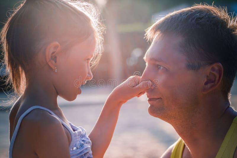Den gulliga lilla flickan och hennes stiliga fader talar och ler Dottern trycker på hans näsa för farsa` s arkivbilder