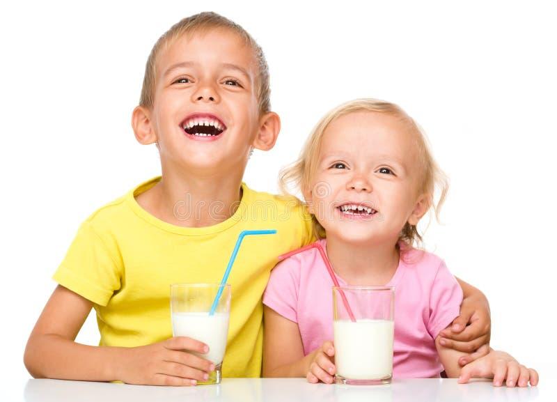 Den gulliga lilla flickan och pojken dricker mjölkar arkivfoton