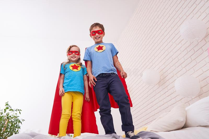 Den gulliga lilla flickan och pojken står på sängen som får klar att flyga, spela superheroen med kappan och maskeringen hemma i  royaltyfri foto