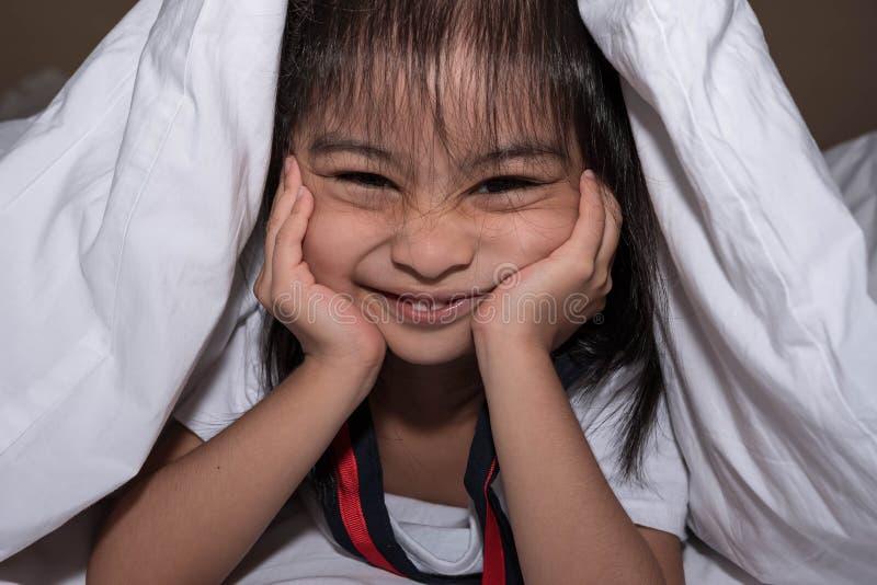 Den gulliga lilla flickan på sängen vaknade upp i morgonen i hennes säng mjuk vit säng för ett barn som döljer under filten royaltyfri bild
