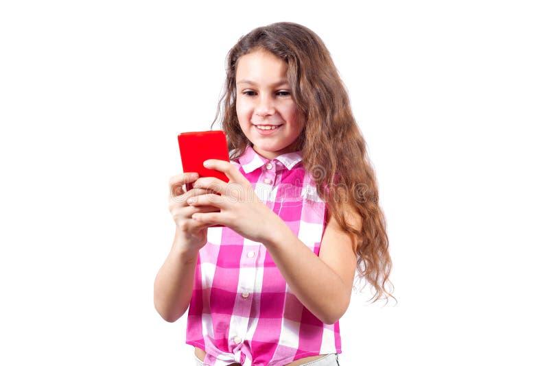 Den gulliga lilla flickan ser, i smartphone och att le fotografering för bildbyråer