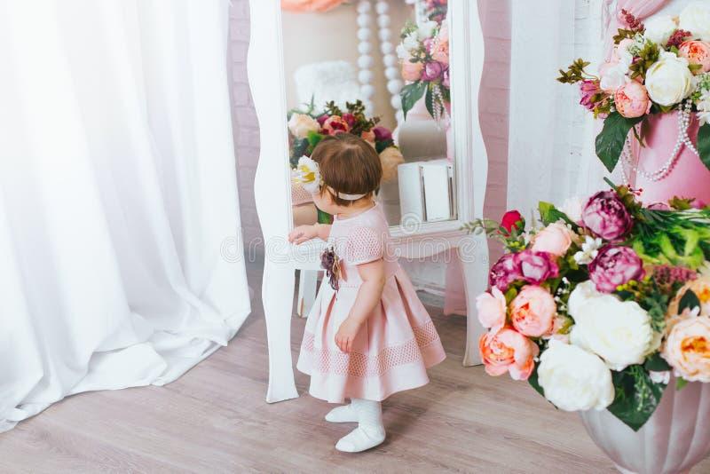 Den gulliga lilla flickan ser i spegeln arkivbild