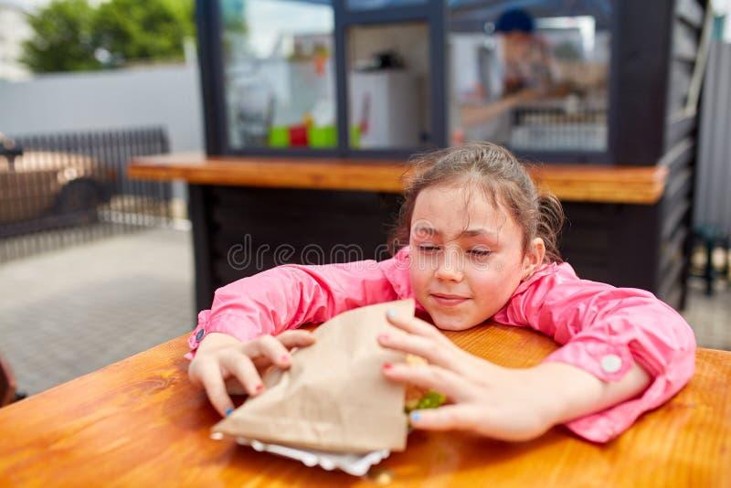 Den gulliga lilla flickan ska äta en osthamburgare i kafét för öppen luft royaltyfri bild