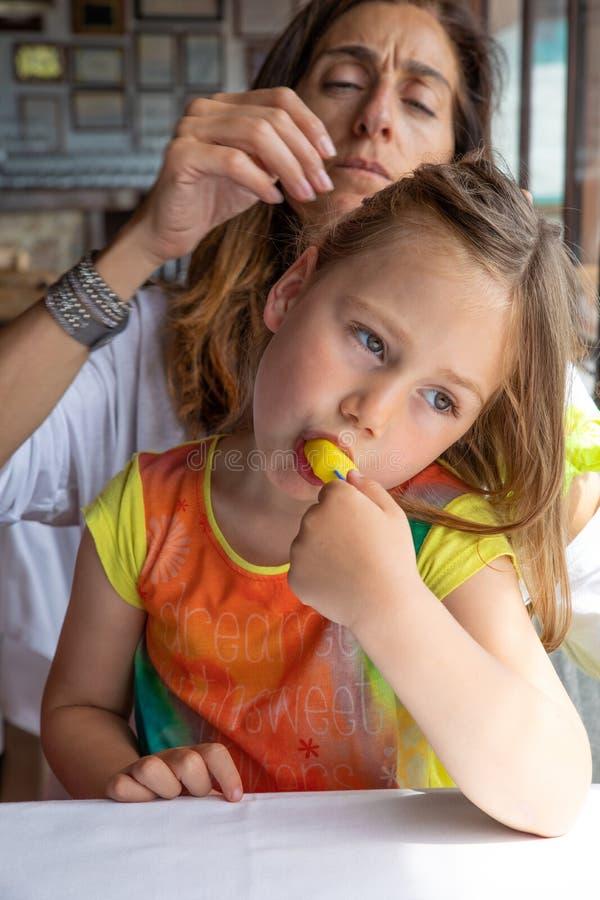 Den gulliga lilla flickan som äter isglassen som sitter på moderben vilar in arkivfoto