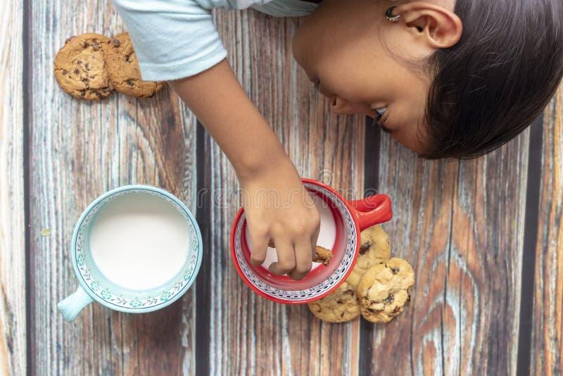 Den gulliga lilla flickan som äter kakor med, mjölkar arkivbild