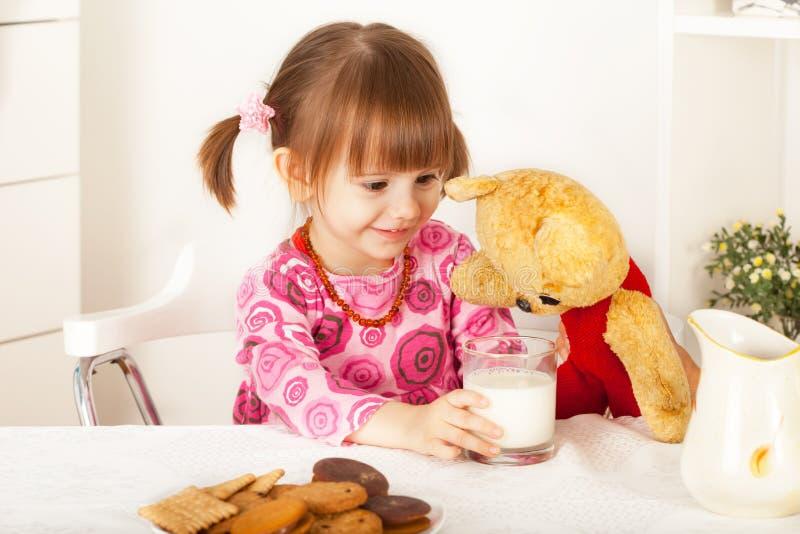 Den gulliga lilla flickan som ger exponeringsglas av, mjölkar till nallebjörnen arkivbilder