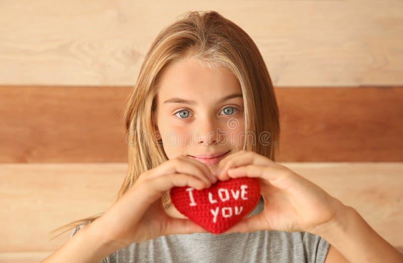 Den gulliga lilla flickan som rymmer hjärta med text ÄLSKAR JAG, DIG på träbakgrund arkivbilder