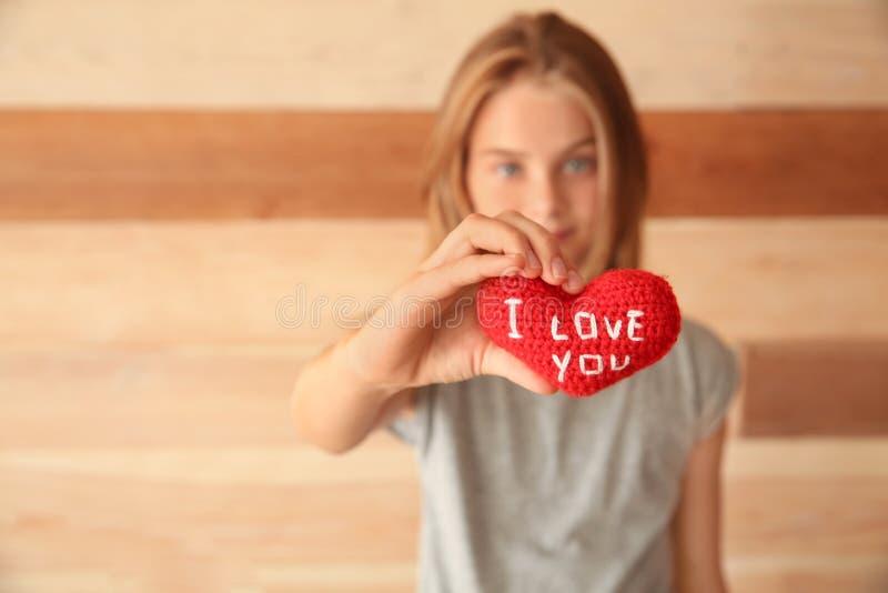Den gulliga lilla flickan som rymmer hjärta med text ÄLSKAR JAG, DIG på träbakgrund royaltyfri bild