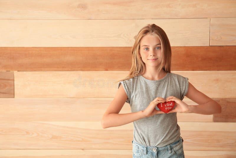 Den gulliga lilla flickan som rymmer hjärta med text ÄLSKAR JAG, DIG på träbakgrund royaltyfri foto
