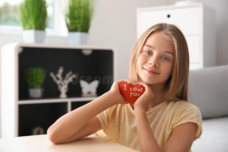 Den gulliga lilla flickan som rymmer röd hjärta med text ÄLSKAR JAG, DIG hemma royaltyfri fotografi