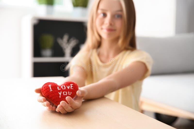 Den gulliga lilla flickan som rymmer röd hjärta med text ÄLSKAR JAG, DIG hemma arkivfoto