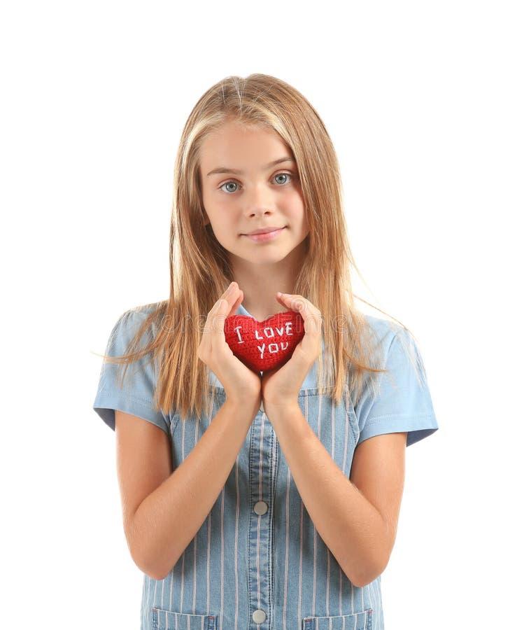Den gulliga lilla flickan som rymmer röd hjärta med text ÄLSKAR JAG, DIG på vit bakgrund royaltyfri foto