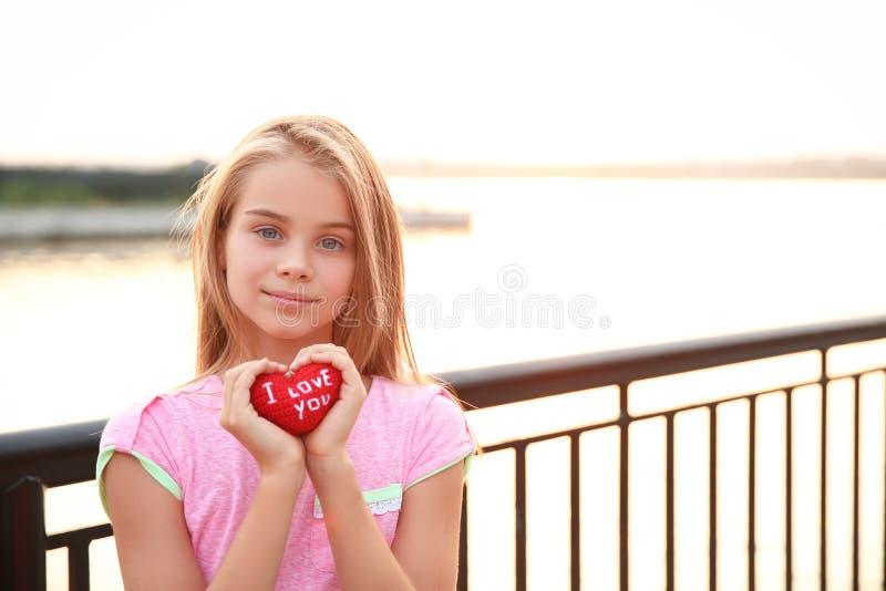 Den gulliga lilla flickan som rymmer röd hjärta med text ÄLSKAR JAG, DIG utomhus arkivbild