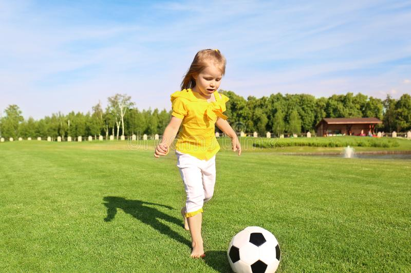 Den gulliga lilla flickan som spelar fotboll parkerar in, på solig dag arkivbild