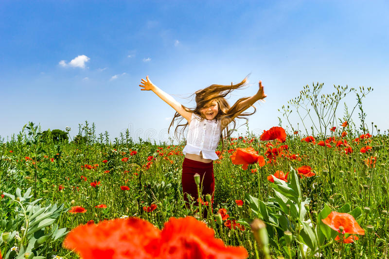 Den gulliga lilla flickan som spelar i röda vallmo, sätter in sommardagen, skönhet arkivfoto