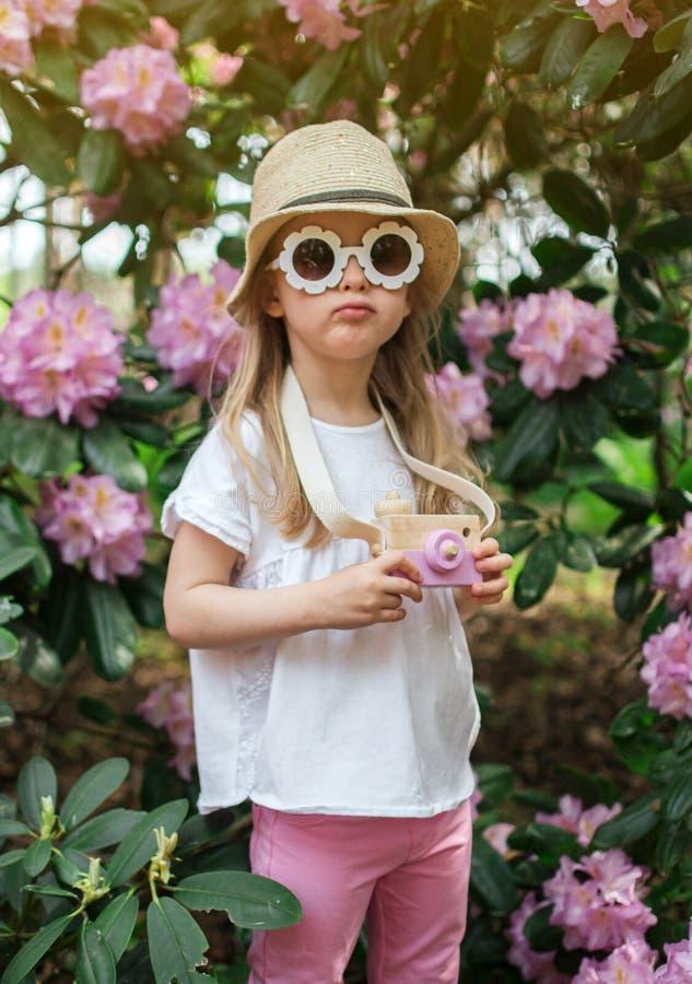 Den gulliga lilla flickan som spelar med barns träkamera i, parkerar med rhododendronblommor royaltyfria bilder