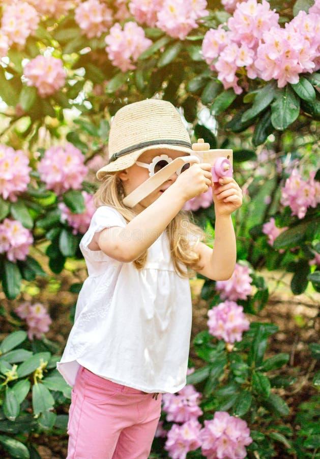 Den gulliga lilla flickan som spelar med barns tr?kamera i, parkerar med rhododendronblommor arkivfoto