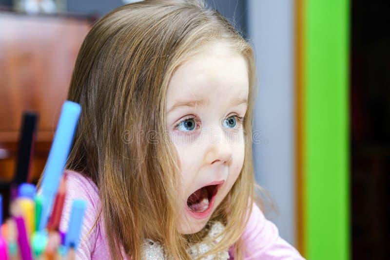 Den gulliga lilla flickan som studing till att tala och att skriva, märker hemma royaltyfria foton