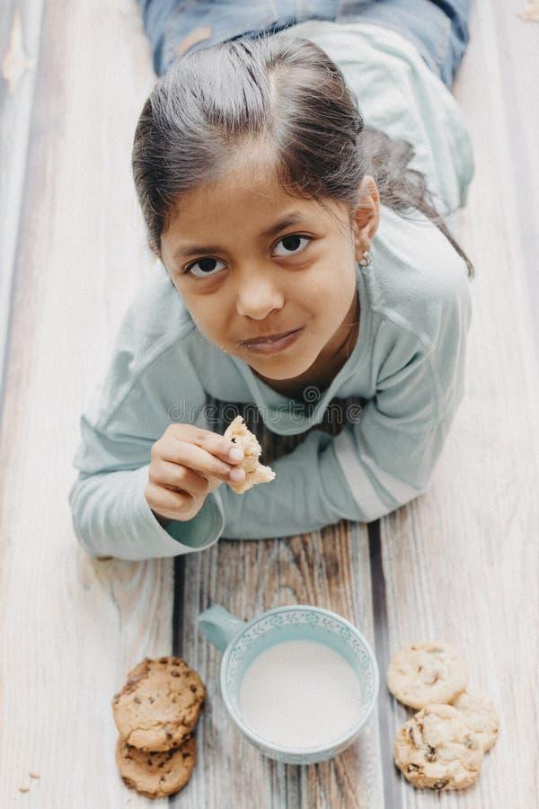 Den gulliga lilla flickan som ?ter kakor med, mj?lkar royaltyfri foto