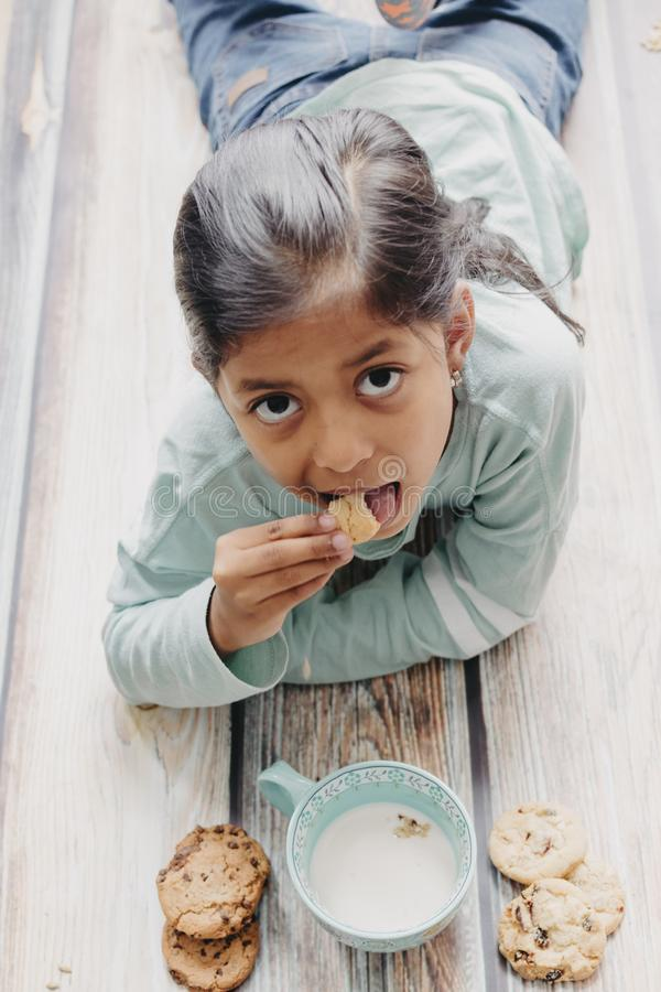 Den gulliga lilla flickan som ?ter kakor med, mj?lkar royaltyfria foton