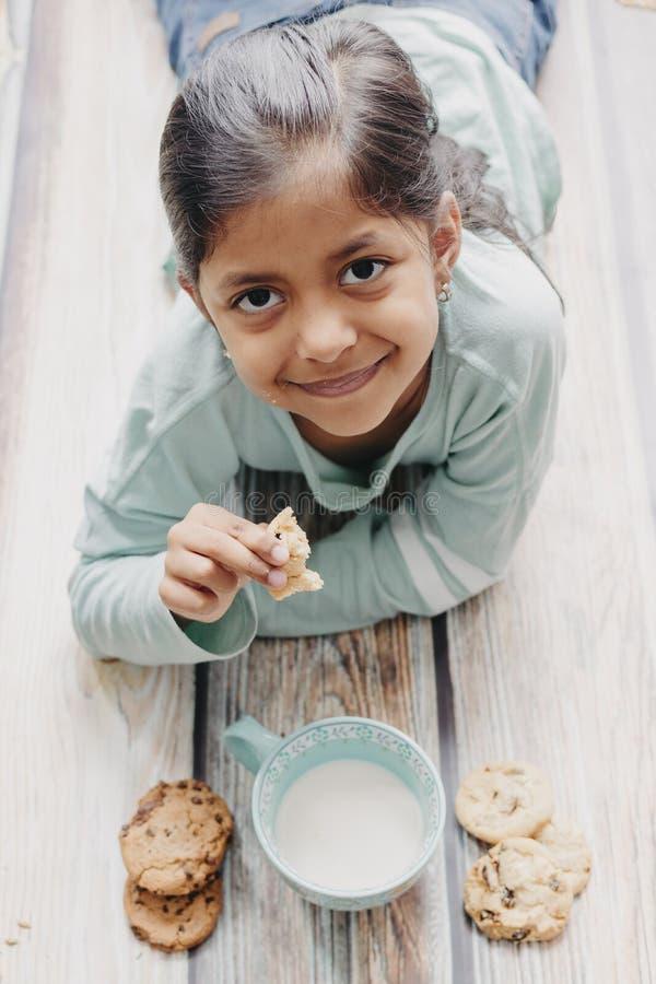 Den gulliga lilla flickan som ?ter kakor med, mj?lkar arkivbilder