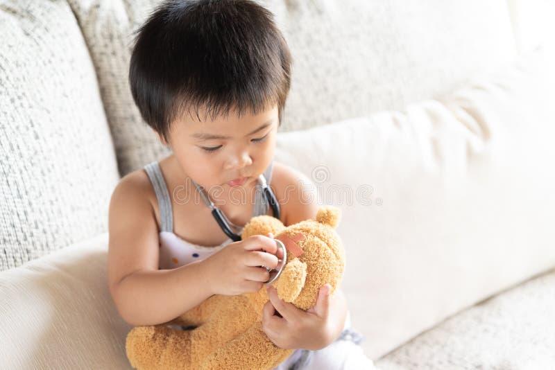 Den gulliga lilla flickan spelar doktorn med stetoskopet och nallebjörnen royaltyfri foto