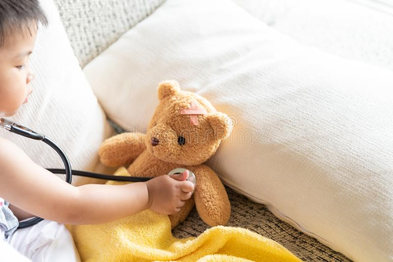 Den gulliga lilla flickan spelar doktorn med stetoskopet och nallebjörnen arkivfoto