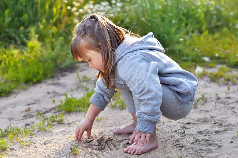 Den gulliga lilla flickan spelar med sand i skogen fotografering för bildbyråer