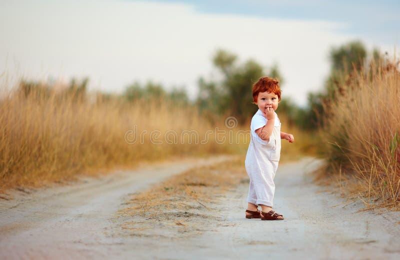 Den gulliga lilla rödhåriga mannen behandla som ett barn pojken som går på den lantliga banan på sommardagen royaltyfria bilder