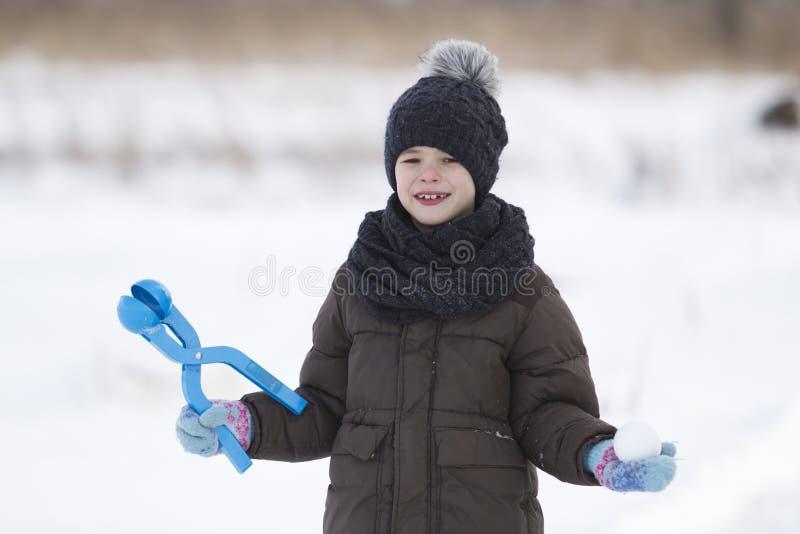 Den gulliga lilla unga roliga tandlösa barnpojken i varma kläder som spelar ha rolig danande, kastar snöboll på kall dag för vint royaltyfria foton