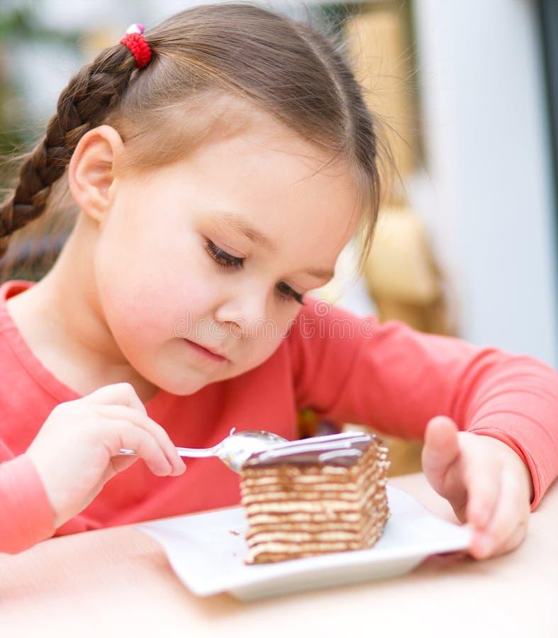 Liten flicka äter tårtan i mottagningsrum arkivbild