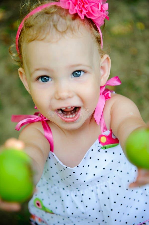 Den gulliga liten flicka ger gröna äpplen arkivbilder