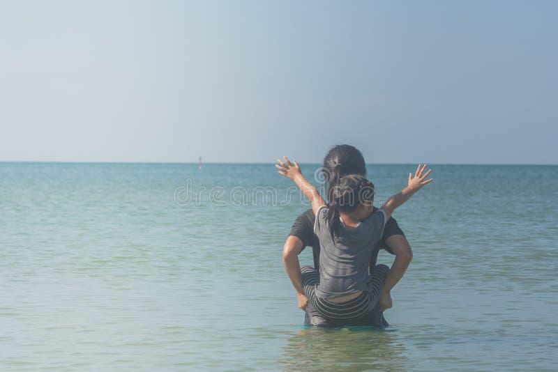 Den gulliga liten flickaridningen på kvinnabaksida och lyfter hennes handfast utgift i havet, dem som ser seascape royaltyfria foton
