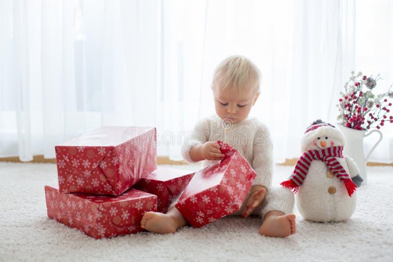Den gulliga litet barnpojken, sötsak behandla som ett barn och att öppna framlägger hemma fotografering för bildbyråer