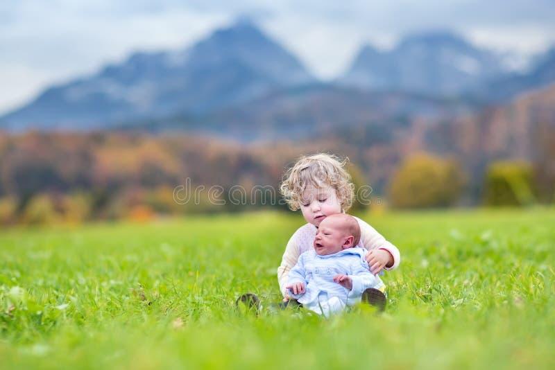 Den gulliga lockiga litet barnflickan och hennes nyfött behandla som ett barn brodern som in spelar royaltyfri fotografi