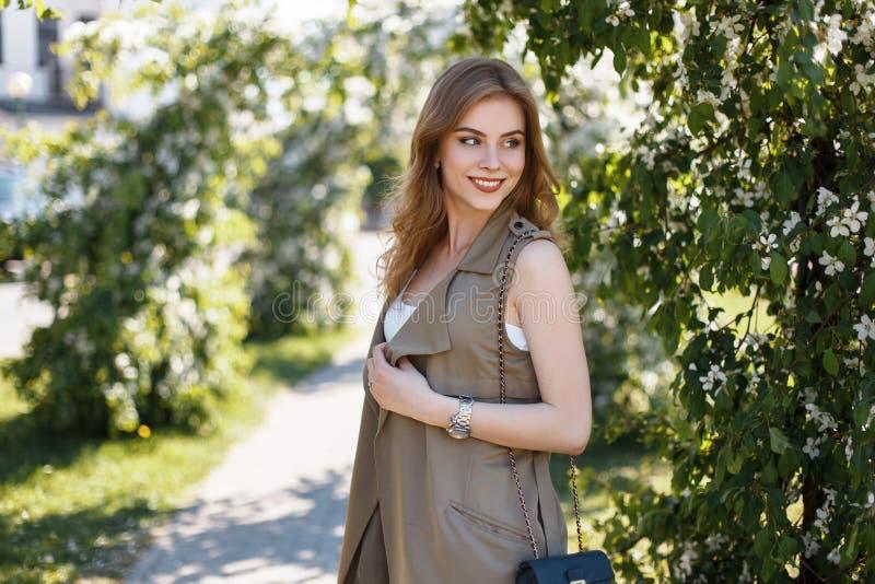 Den gulliga lyckliga attraktiva unga kvinnan i en stilfull sommar tilldelar en vit T-tröja med en svart piskar handväskan som pos royaltyfria foton