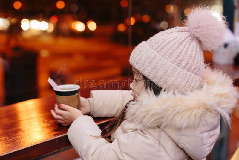 Den gulliga lyckliga lilla flickan dricker varmt te i ett gatakafé arkivbilder