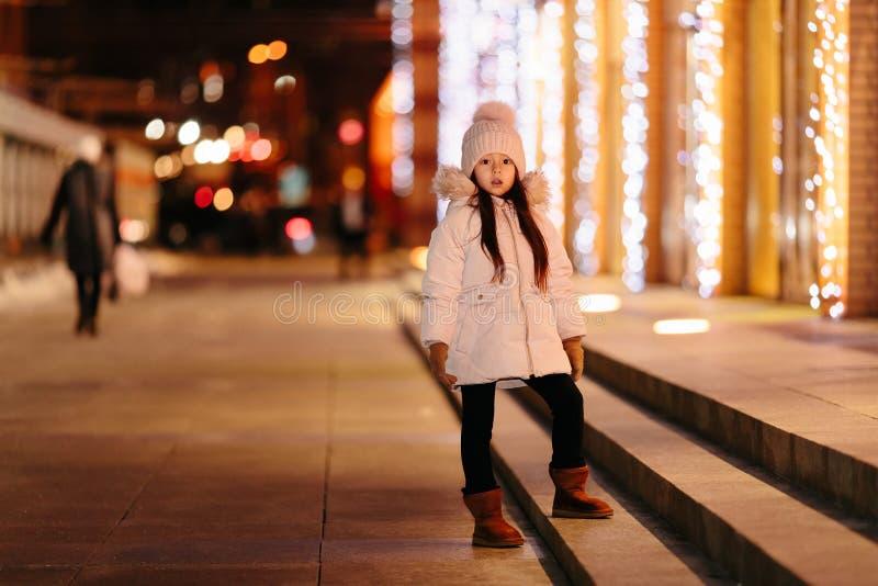 Den gulliga lyckliga lilla flickan går på gatorna av en storstad fotografering för bildbyråer