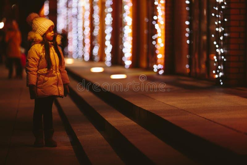 Den gulliga lyckliga lilla flickan går på gatorna av en storstad royaltyfri fotografi