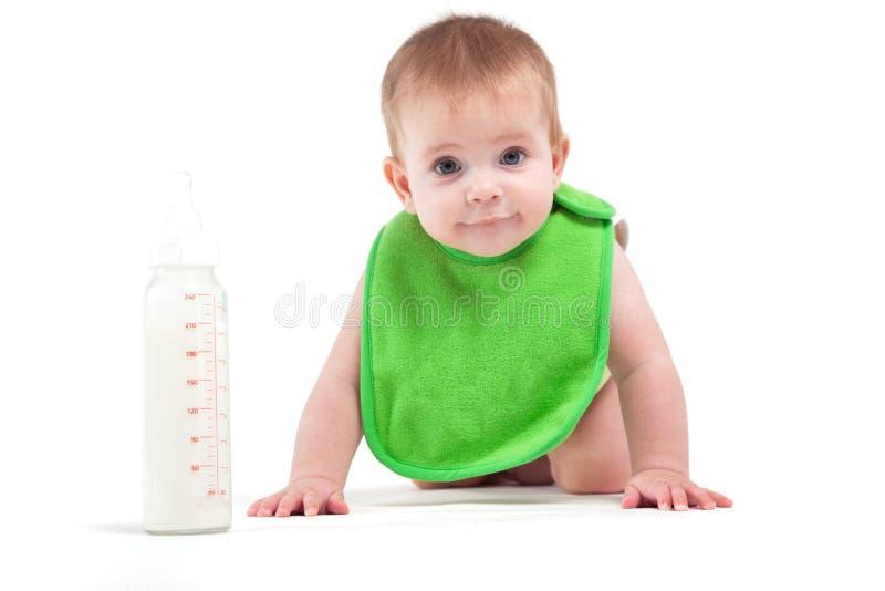 Den gulliga lyckliga pysen i grön haklapp nära mjölkar flaskan fotografering för bildbyråer