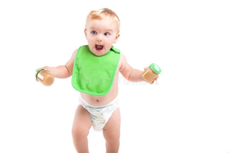 Den gulliga lyckliga pysen i grön haklappställning med behandla som ett barn mat royaltyfria foton